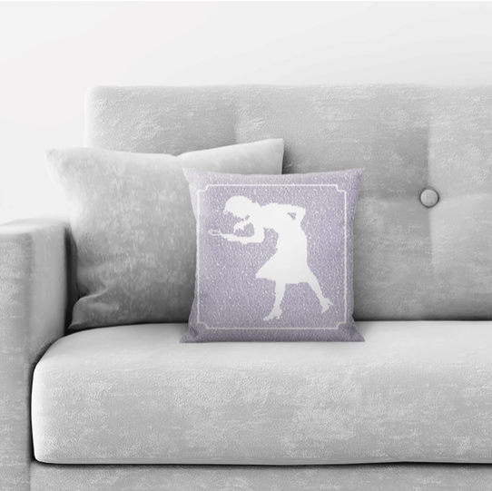 couch with a throw pillow on it with words from a Nancy drew book making up the profile of a woman with a magnifying glass