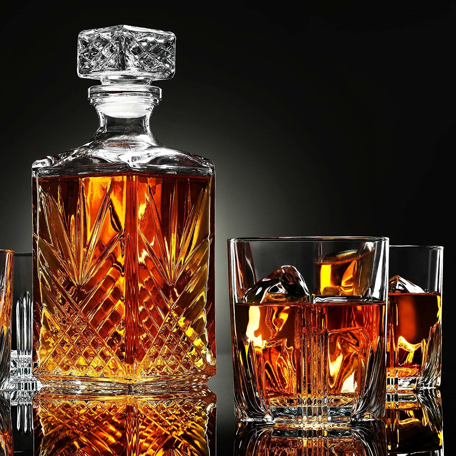 crystal cut decanter and two matching drinking glasses filled with brown liquor