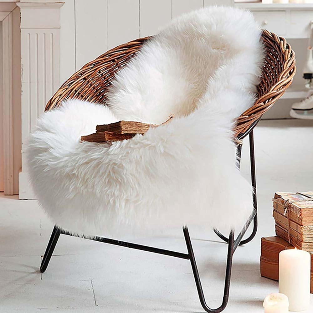 wicker chair with white faux sheepskin rug thrown on it