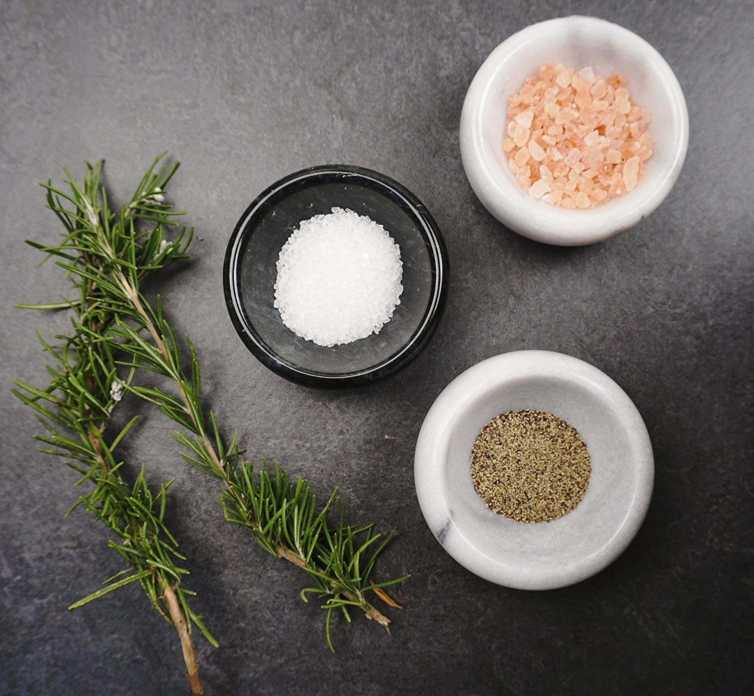 Top shot image of a sprig of thyme and marble bowls with different seasonings inside each