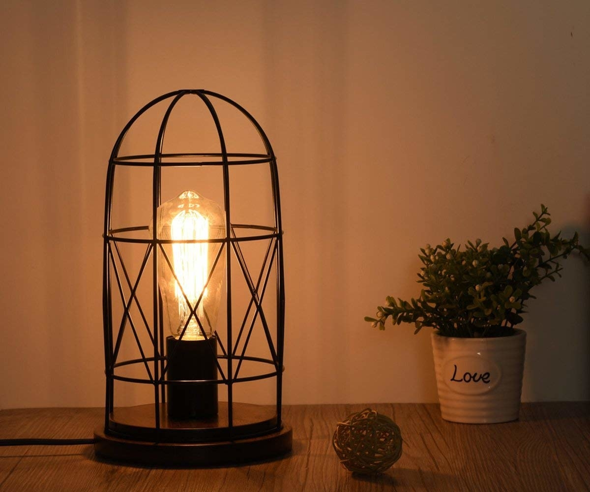 small table lamp with edison-style bulb with a black cage around it
