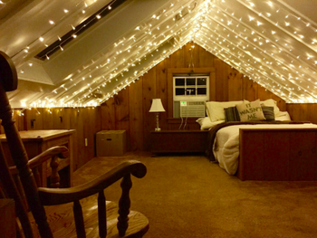 reviewer pic of lighted curtains on an A-frame ceiling in an attic bedroom