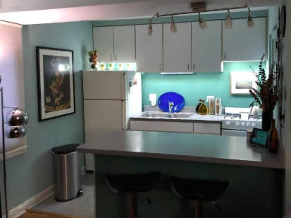 kitchen with plain white stock cabinets with lights underneath them to make it look so much better