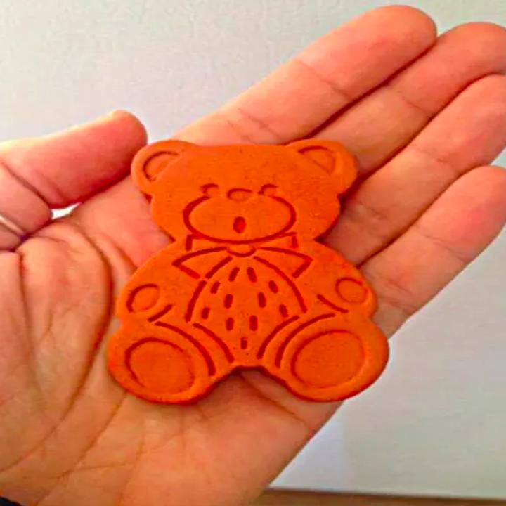 person holding terra-cotta teddy