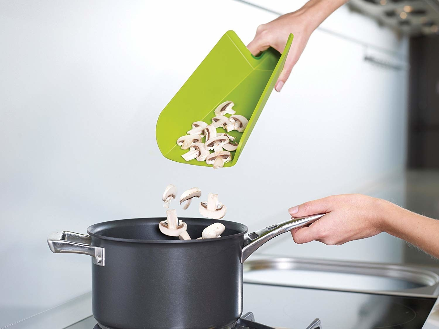 Tri-folded cutting board spilling mushrooms into pot on stovetop