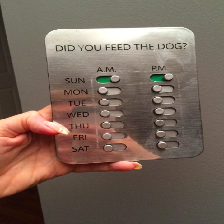 """A hand holding the flat product with the text """"Did you feed the dog?"""" and places to slide a lever indicating if you did for each day of the week in the a.m. and p.m."""