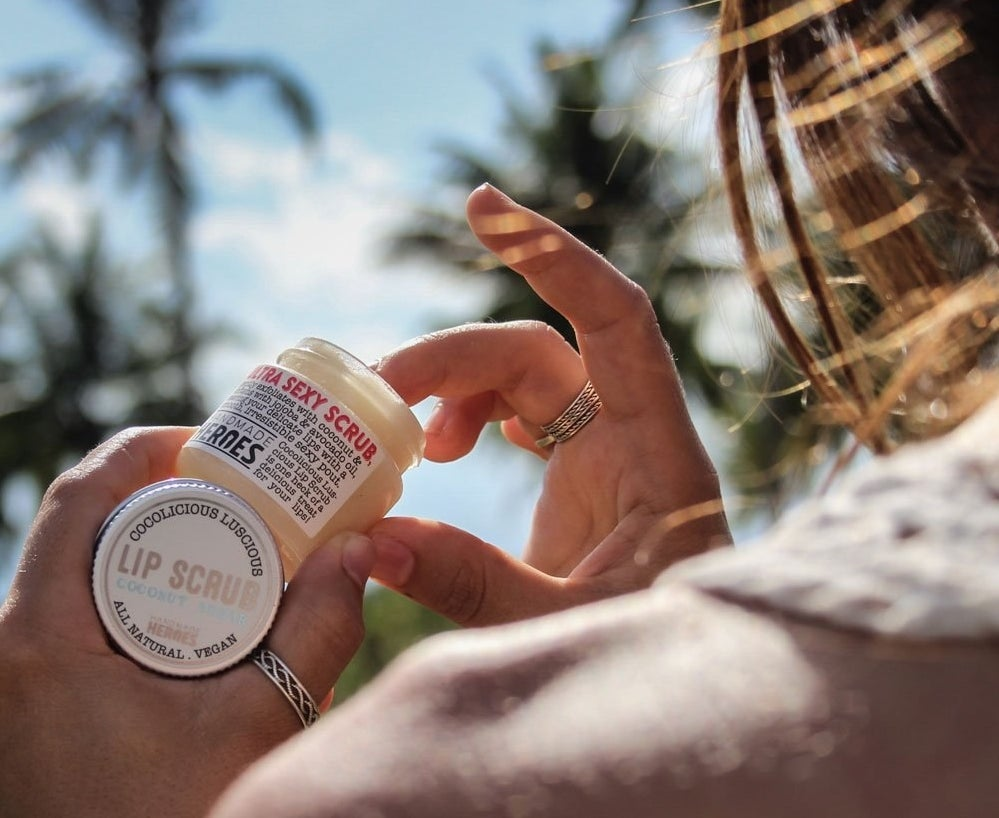 Hand dipping into container of coconut lip scrub