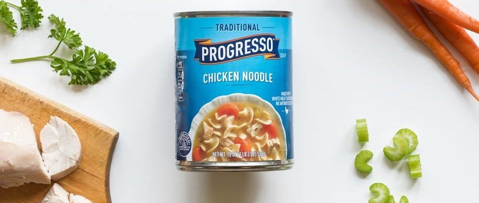 A blue can of Progresso chicken noodle sitting on a wite surface along with chopped celery, carrots, and chicken.