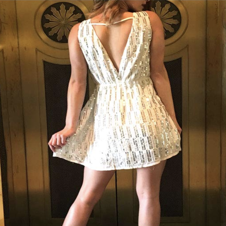 A reviewer in the white dress from the back showing the v-back