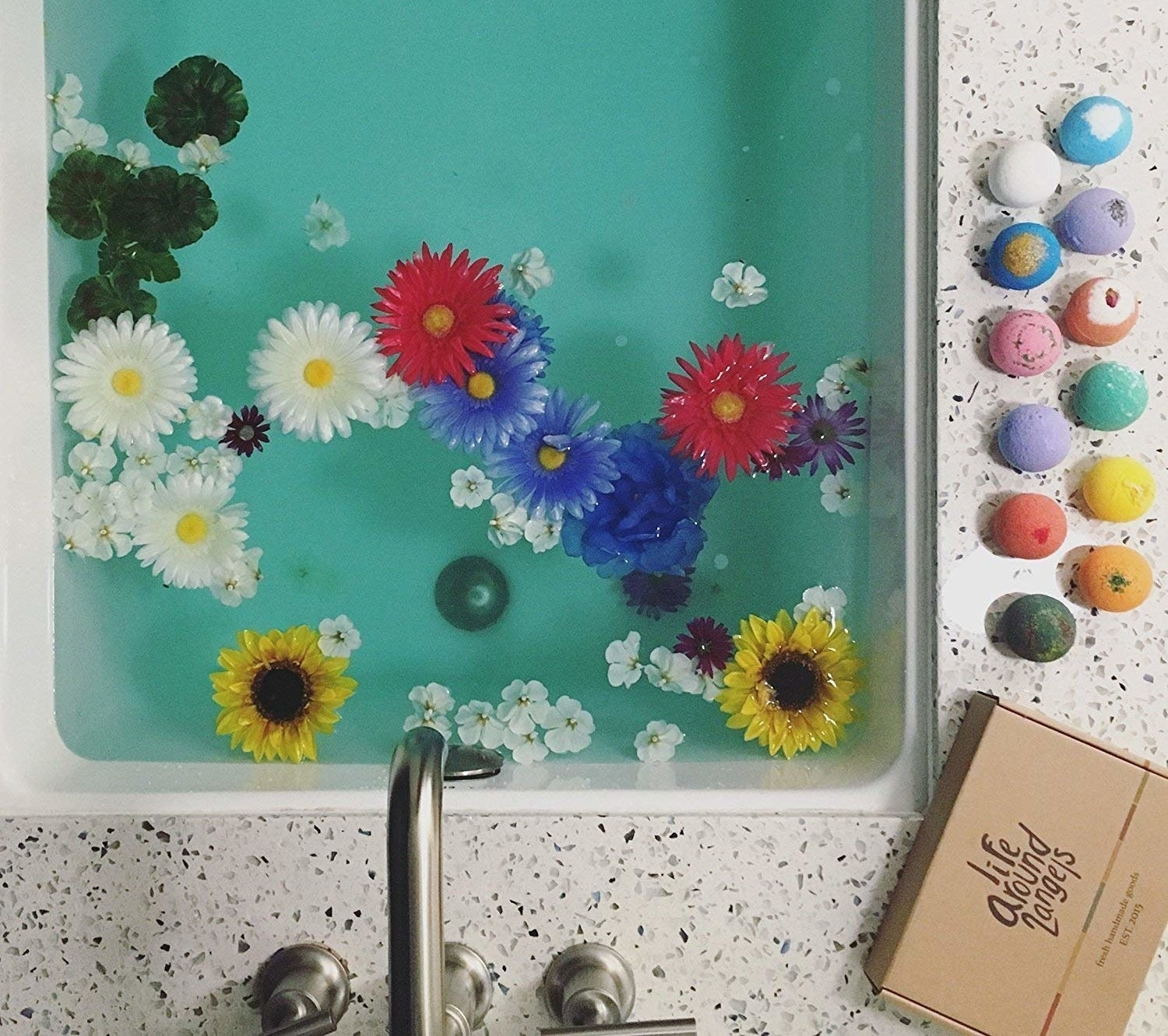 bath tub with flowers in it and bath bombs on the side