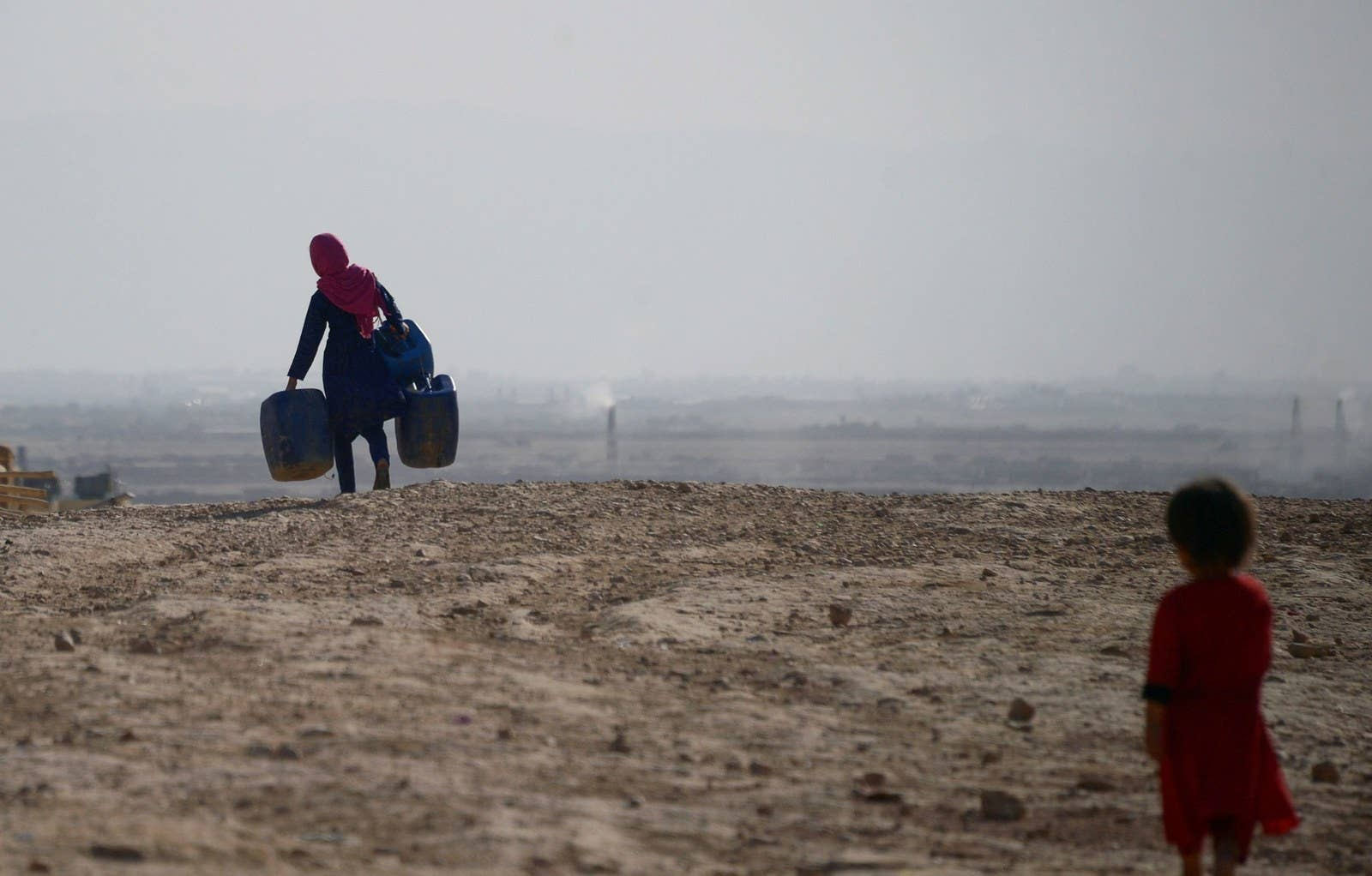 An Afghan girl carries empty containers to collect water as a younger child looks on in Sakhi village, Afghanistan, on July 19.