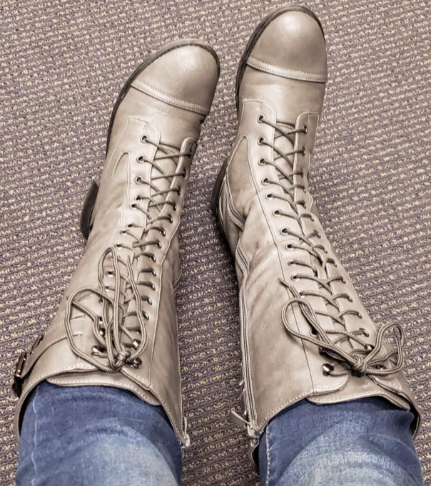reviewer wearing the gray lace-up knee-high boots