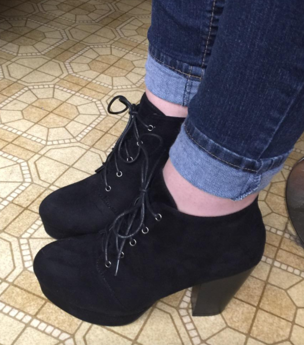 reviewer wearing the black suede lace-up heeled booties
