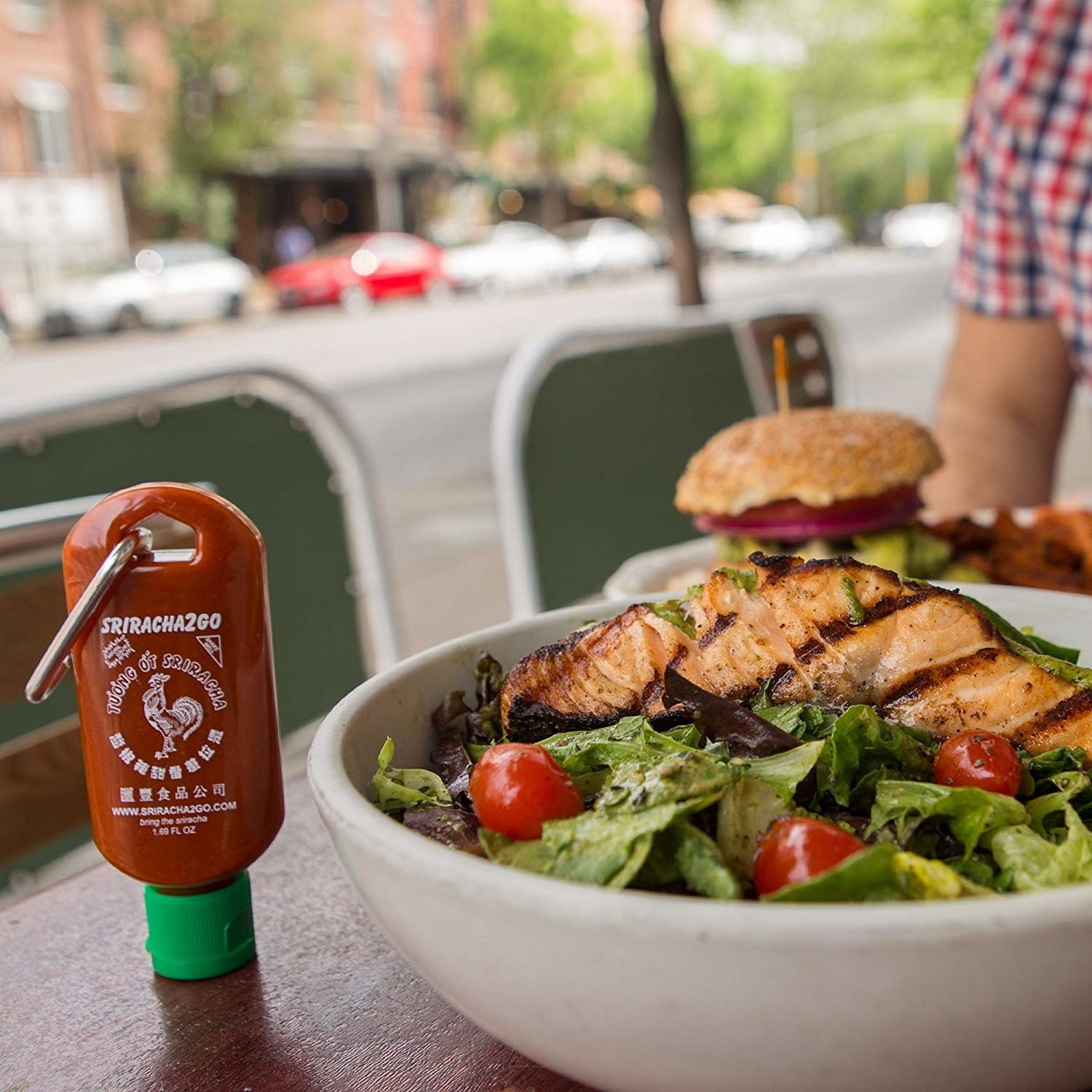 A filled Sriracha bottle keychain beside a meal at a restaurant