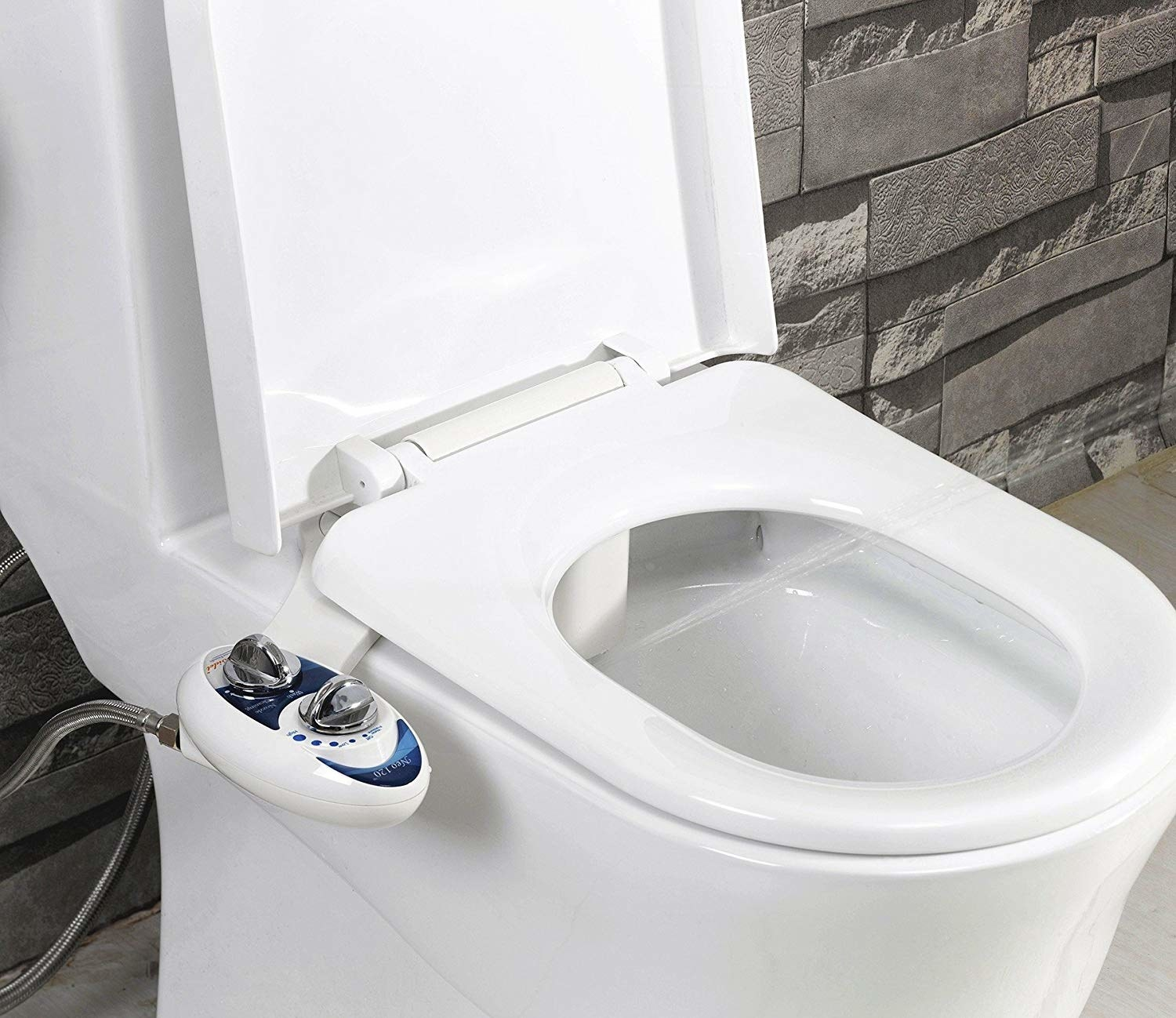 The bidet controls on the side of the toilet, and a jet of water coming out of the bidet inside the bowl