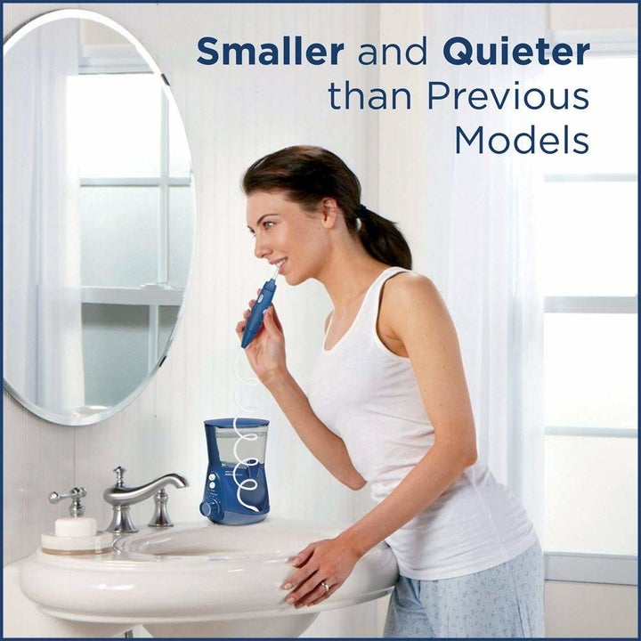 "Model using the waterpik handle with text ""smaller and quieter than previous models"""