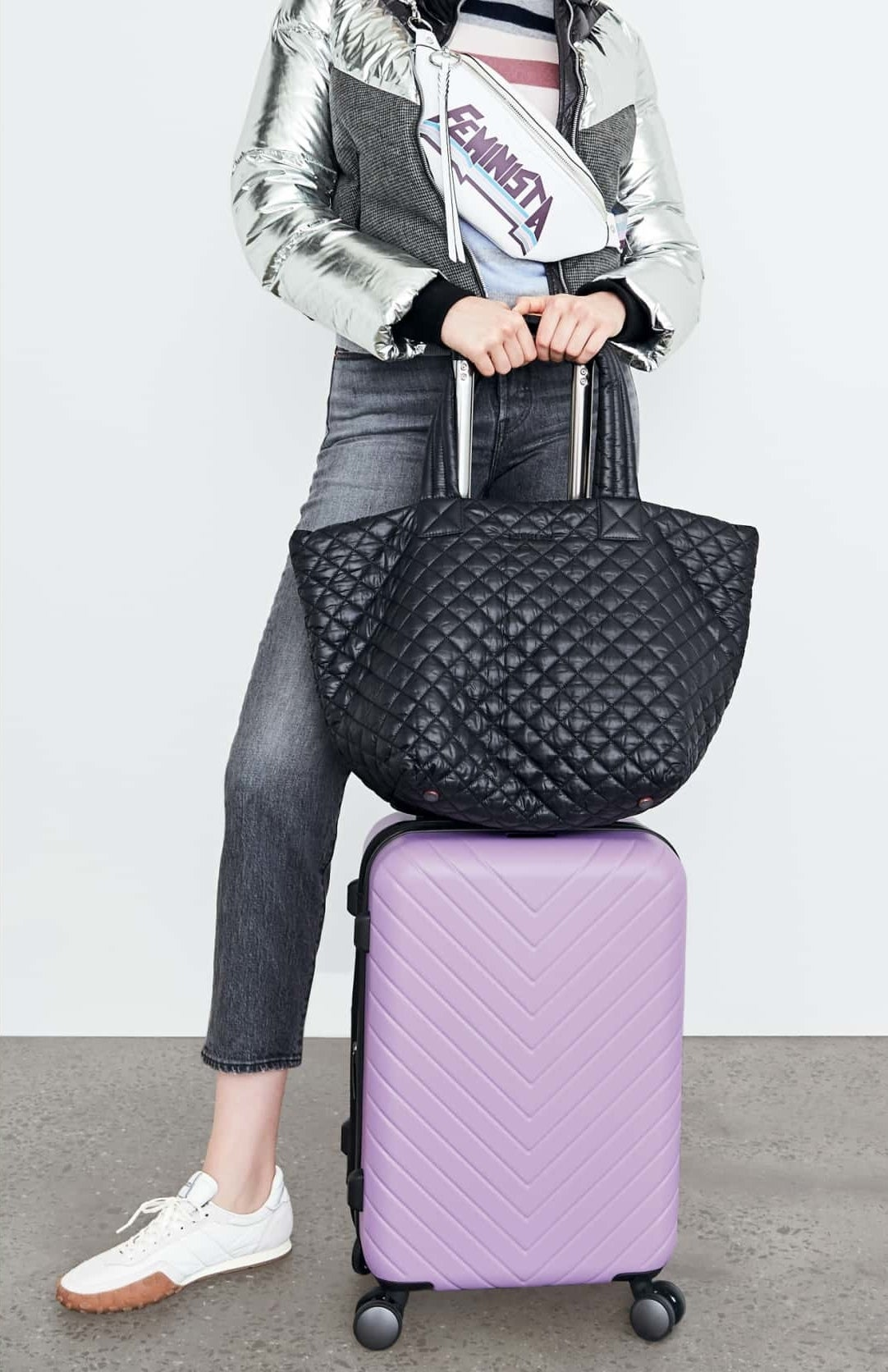 The quilted bag in black sitting on top of a suitcase