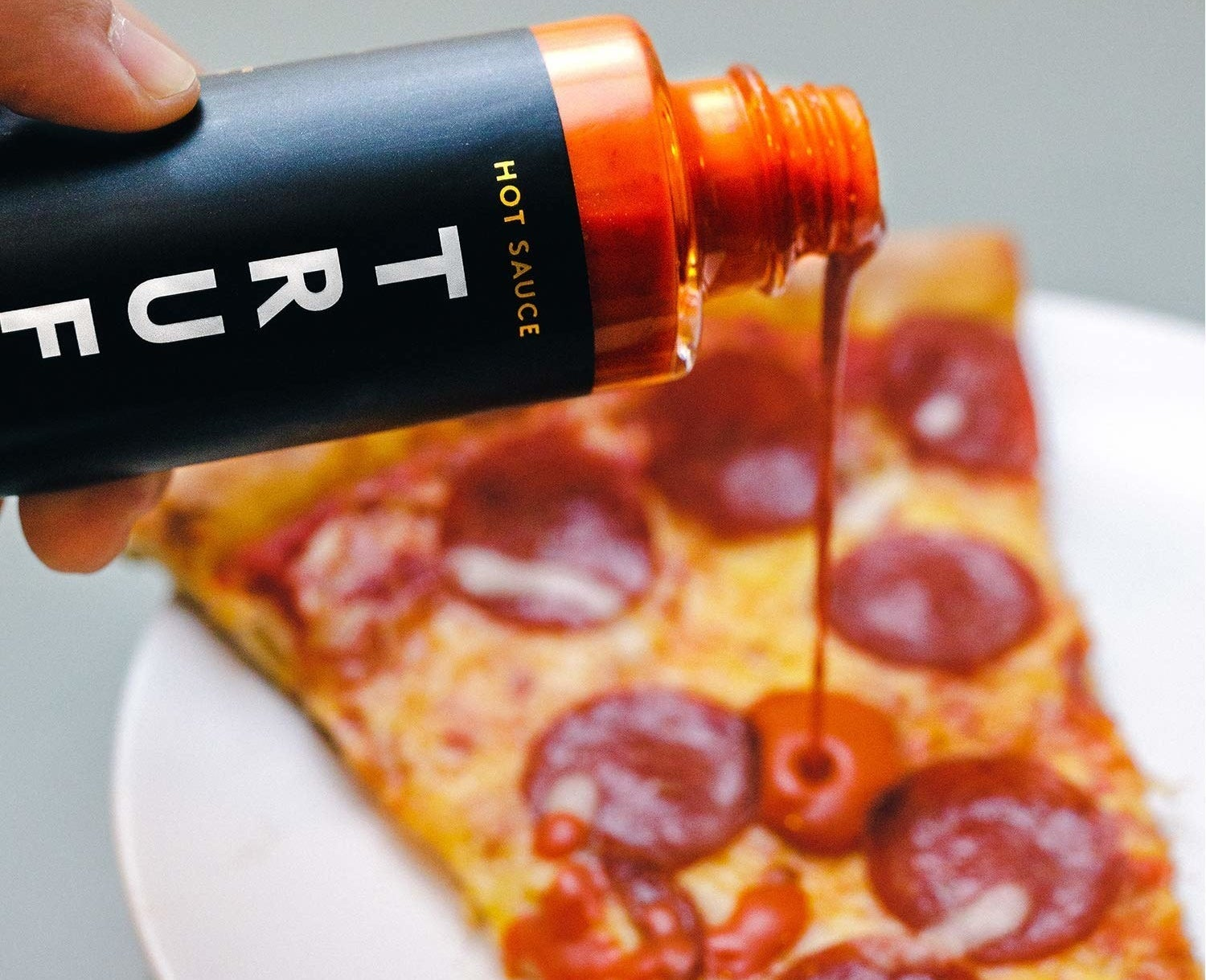 A person putting the truffle hot sauce on pepperoni pizza