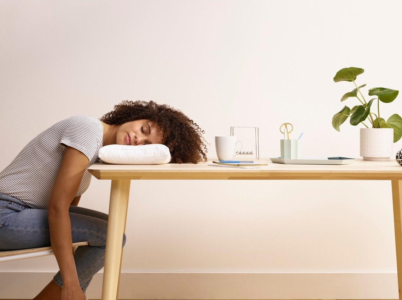 Model using travel pillow to sleep on table
