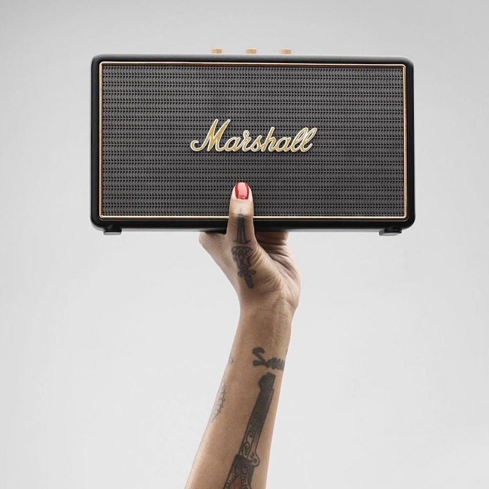 hand holds speaker that looks like amp