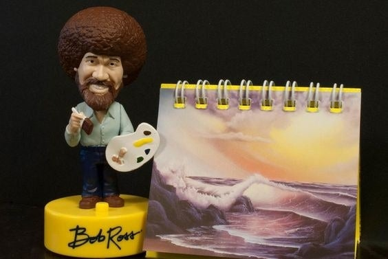 the bob ross bobble head and mini easel featuring Ross's landscape artwork