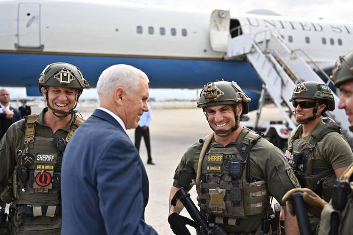 Sgt. Matt Patten, left, was photographed wearing a red QAnon patch on his chest while Vice President Mike Pence in Florida on Friday.