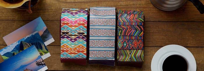 Three bags of coffee with bright and colorful patterns on each bag