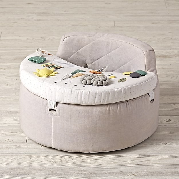 light pink/gray soft chair with a try that has all sorts of soft things for a baby to play with