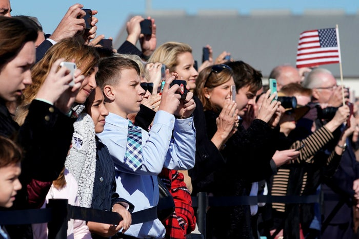 People watch the departure ceremony for former president George H.W. Bush at Ellington Field in Houston on Monday.