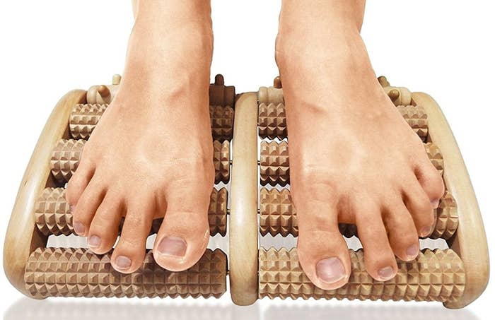 person rolling feet across wooden massager with rolling cylinders on it that are textured with nubs