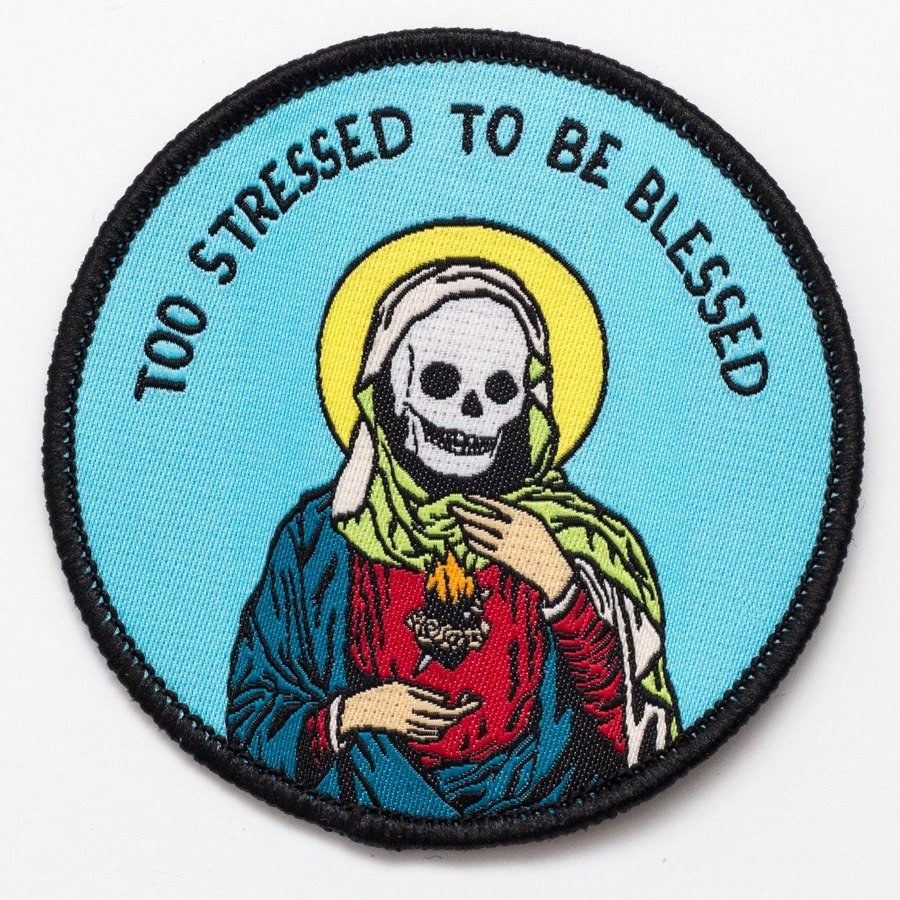 "a circle patch with a scull in the middle and the words ""too stressed to be blessed"" on it"
