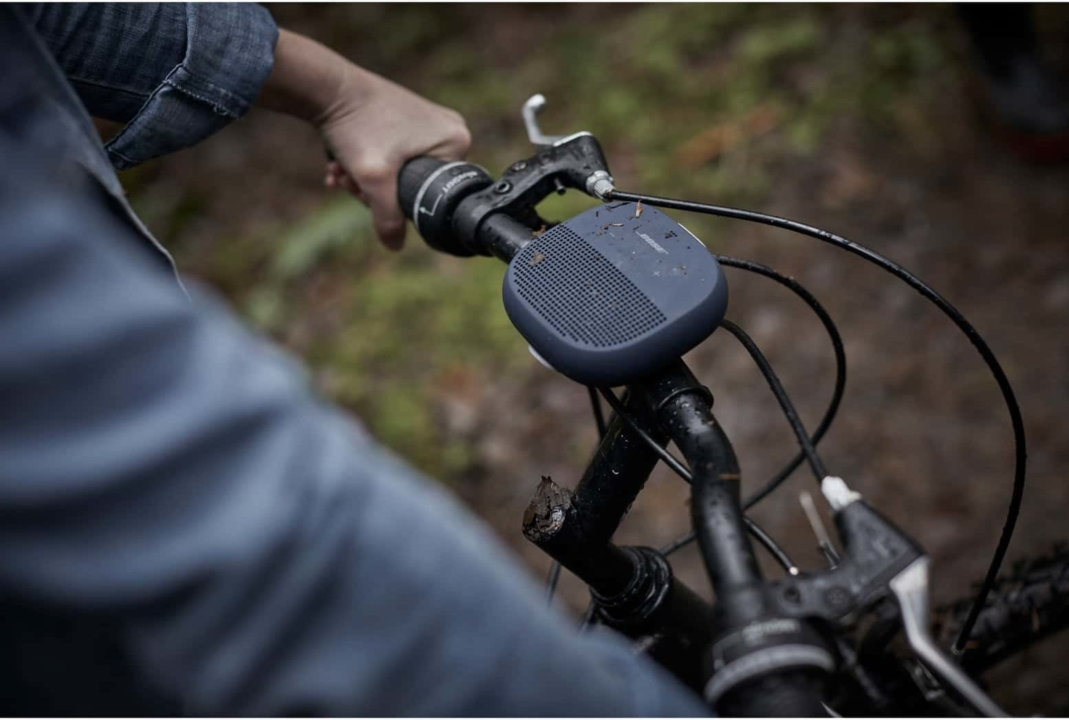 The small square speaker with rounded edges in dark blue on bike handlebars
