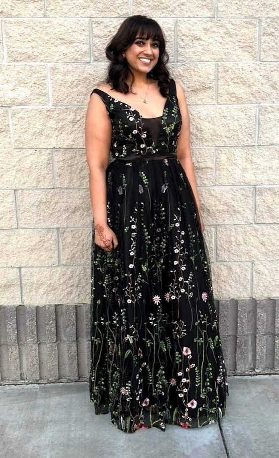 a reviewer wearing a black tulle dress with floral print on it