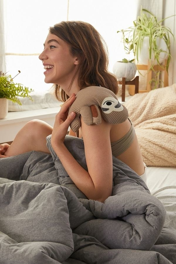 Model holding the sloth pad over shoulder