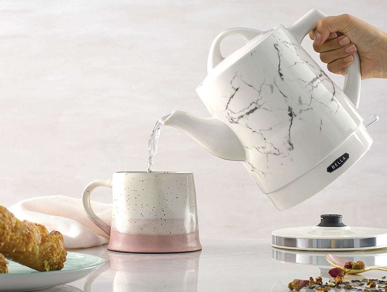 person pouring water from the marble print tea kettle into a coffee mug