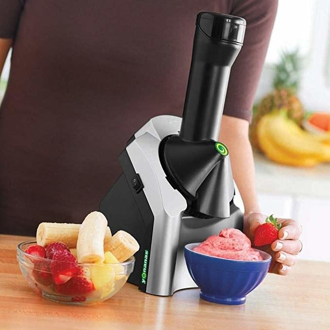 Soft serve machine next to a bowl of fresh fruit and a bowl of soft serve