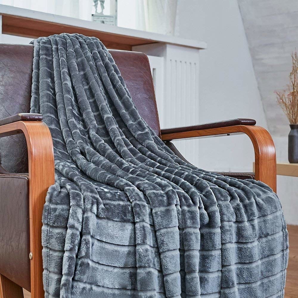 The blanket draped across a chair; it has slight stripes in its pattern