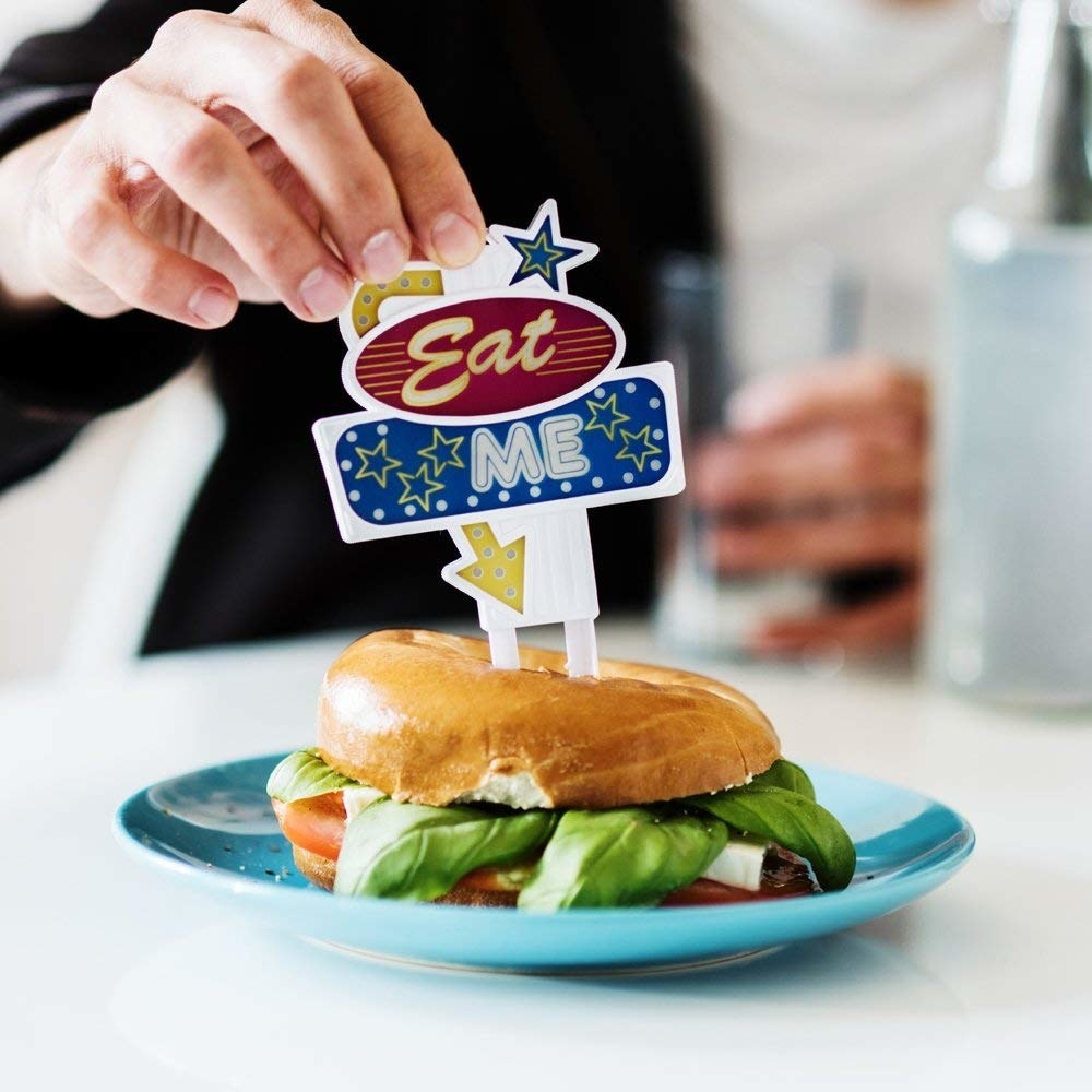 "person sticking an ""eat me"" sign into the top of a burger"