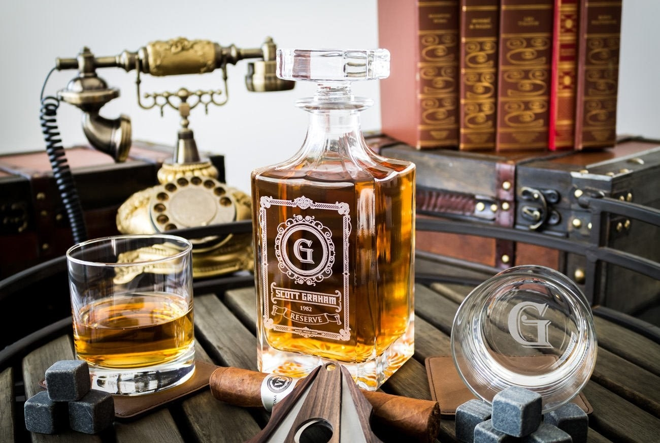 The custom decanter styled on a table with a glass of whiskey and a cigar