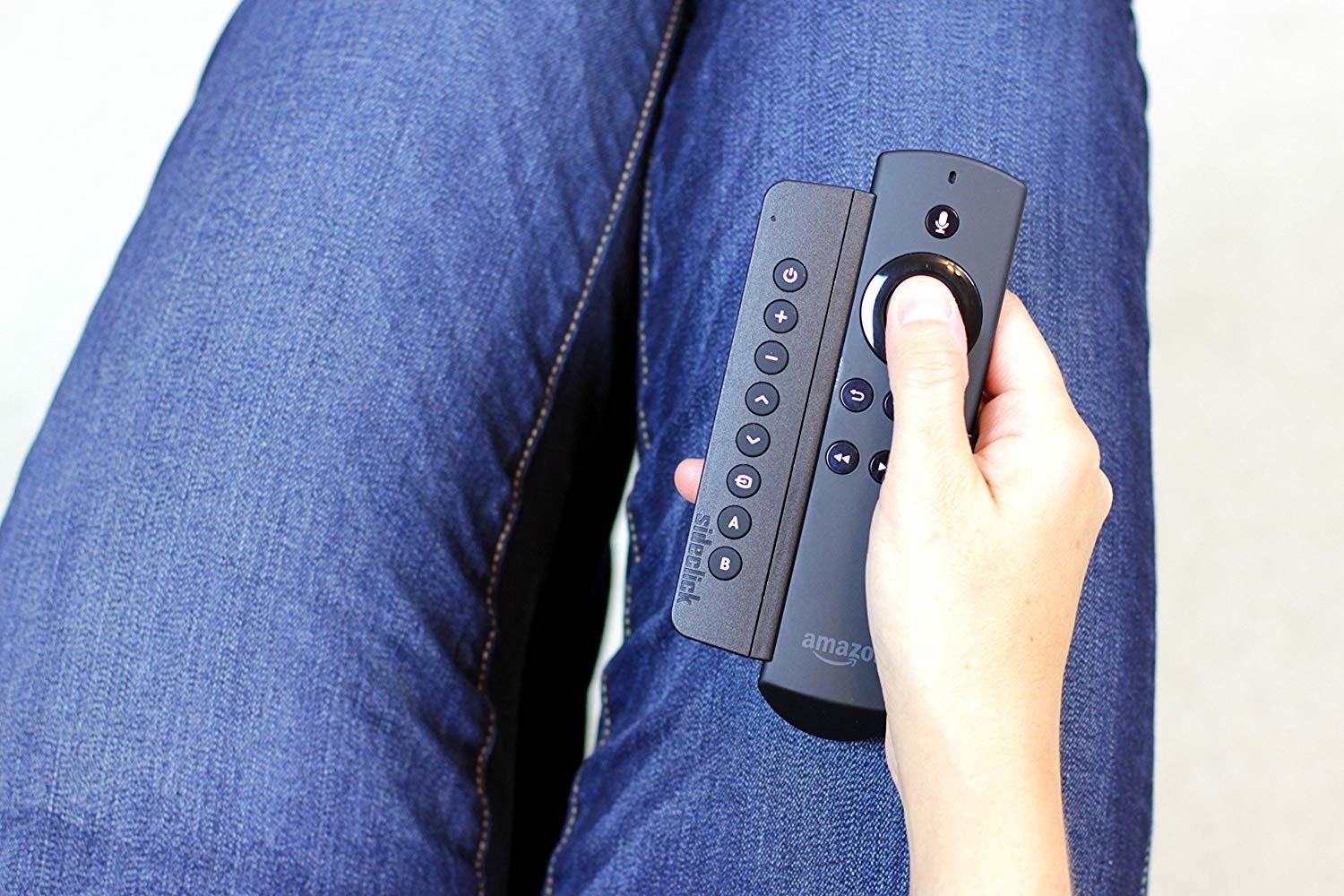 A person holding Fire TV Stick remote with the attachment