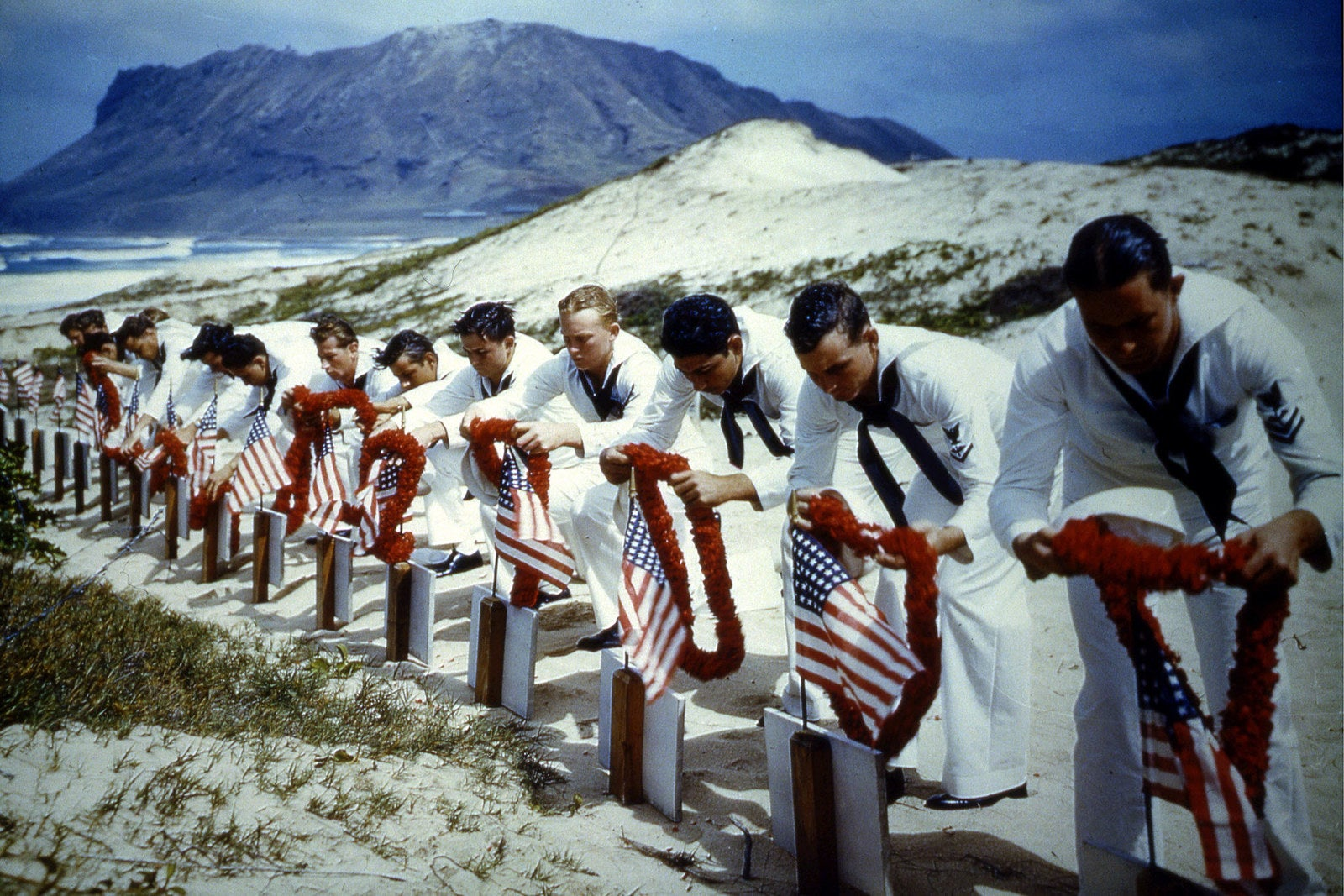 American sailors in Hawaii place leis over the graves of those who died in the attacks on Pearl Harbor during spring 1942.
