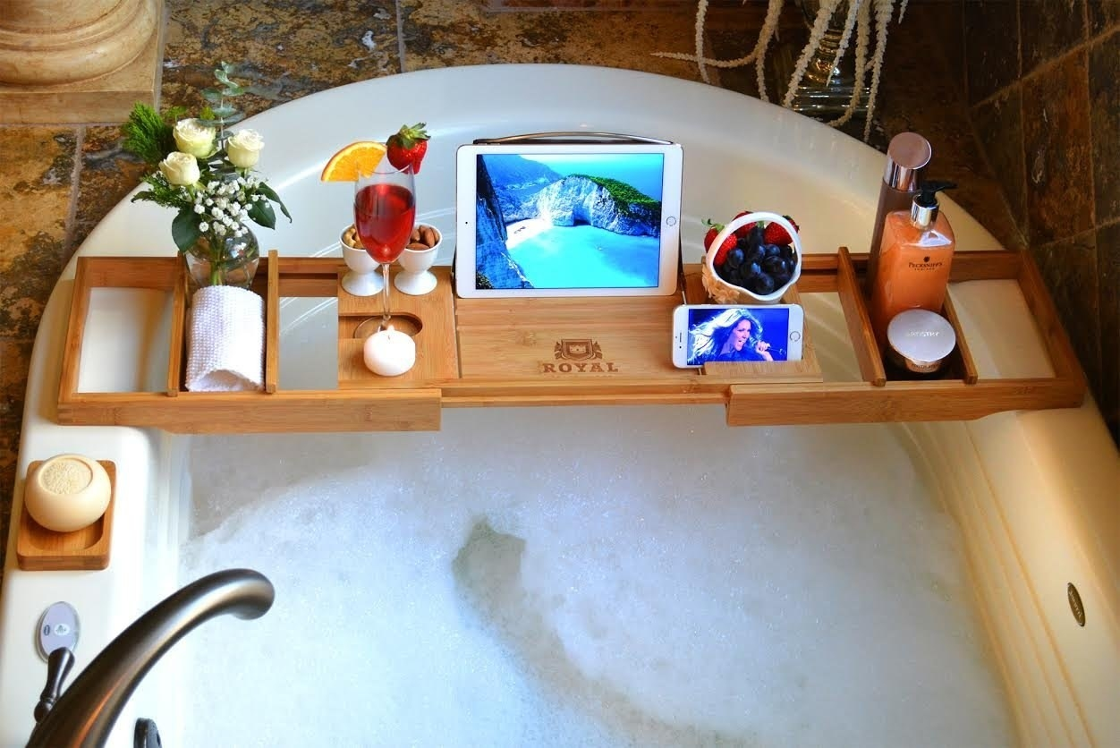 The tub caddy holding an iPad, iPhone, drink, towel, towels, and other bath essentials  balanced over a full tub