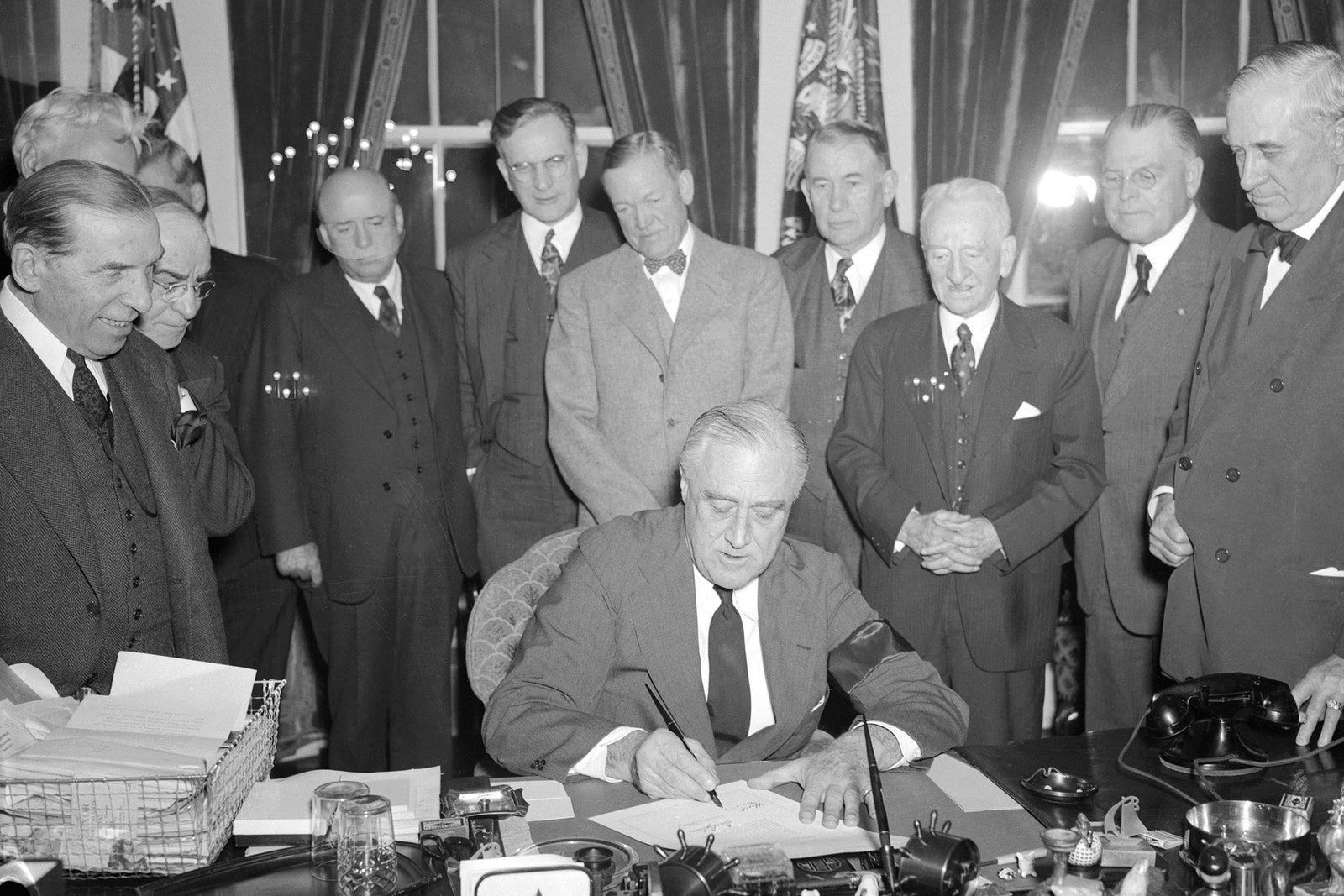 President Franklin D. Roosevelt signs the resolution declaring that a state of war exists between the United States and the Japanese Empire on Dec. 8, 1941.
