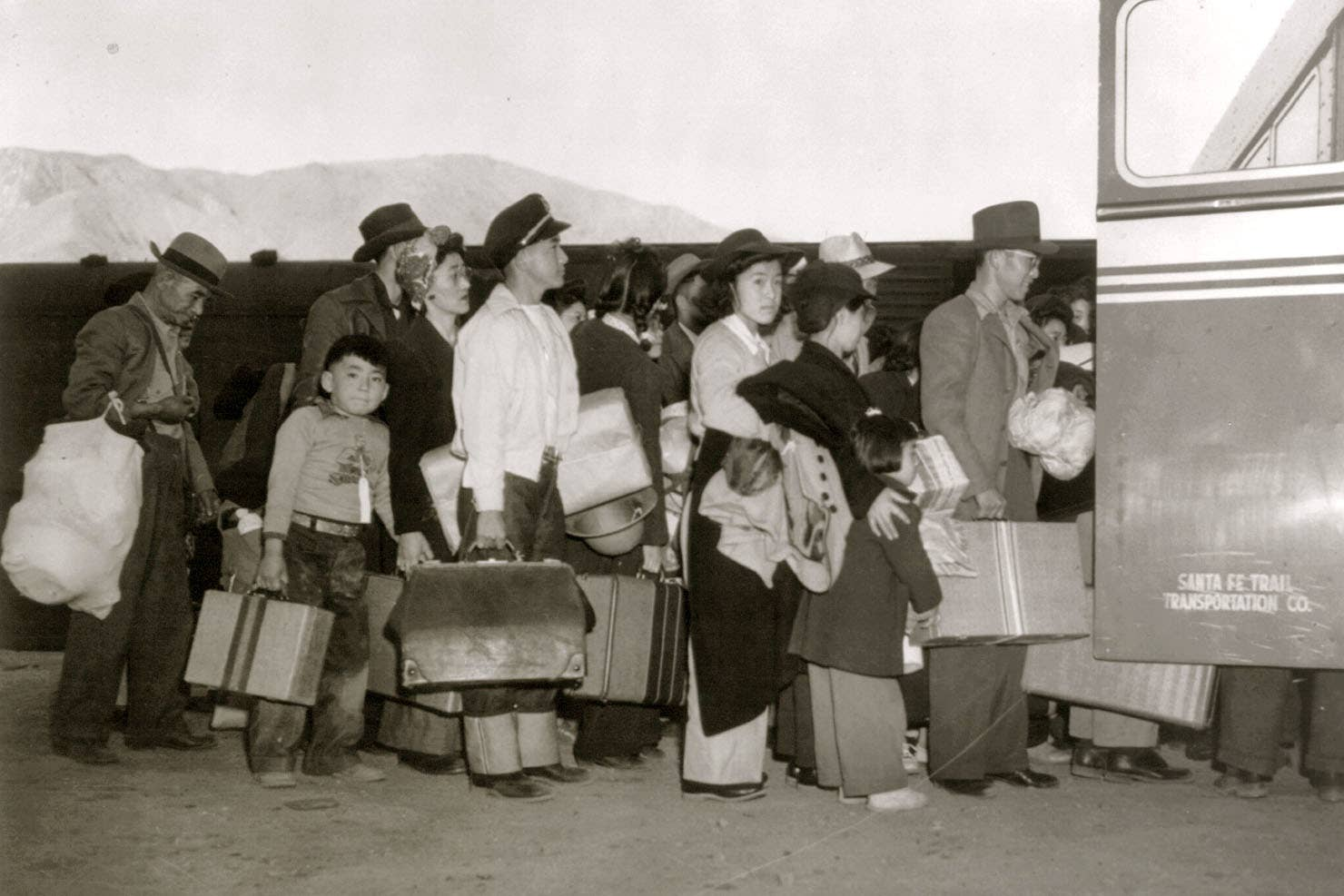 Japanese Americans transfer from train to bus at Lone Pine, California, bound for an internment camp at Manzanar, circa1942.