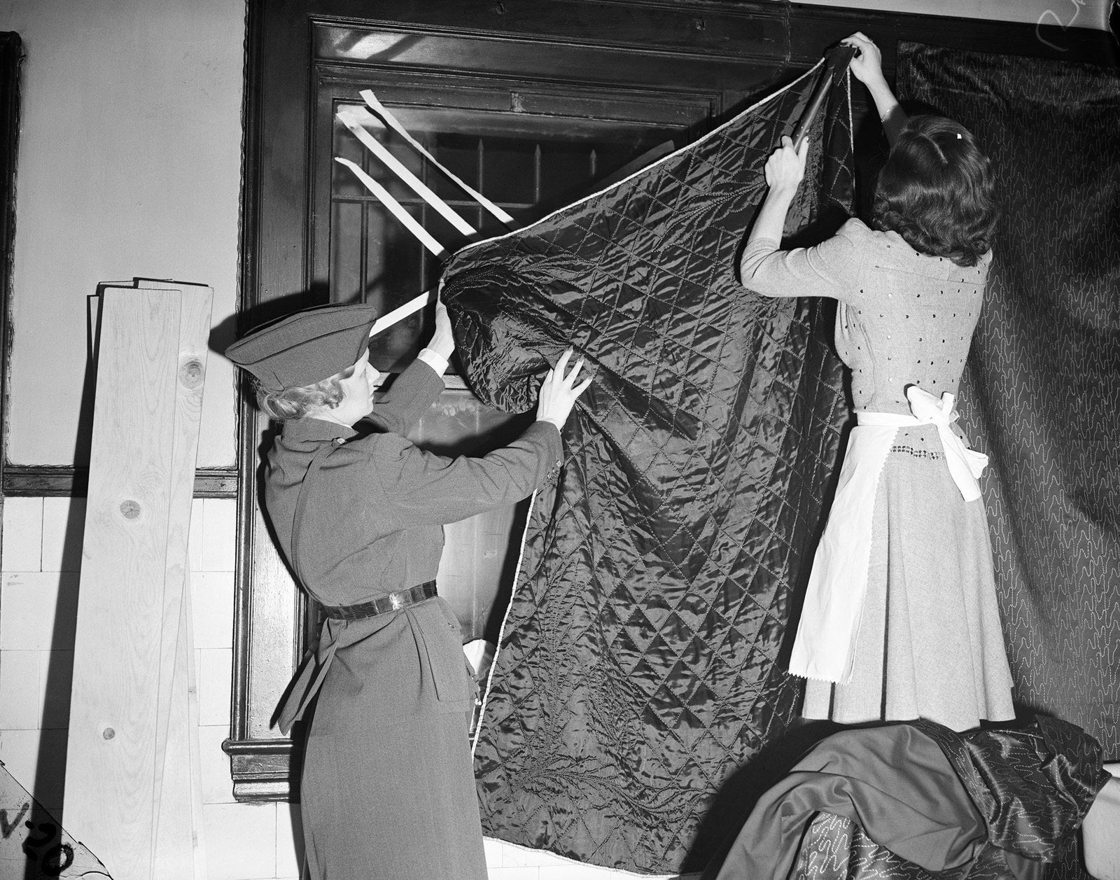 An instructor with the American Women's Voluntary Services demonstrates how to black out windows for defense against air raids on Dec. 13, 1941.