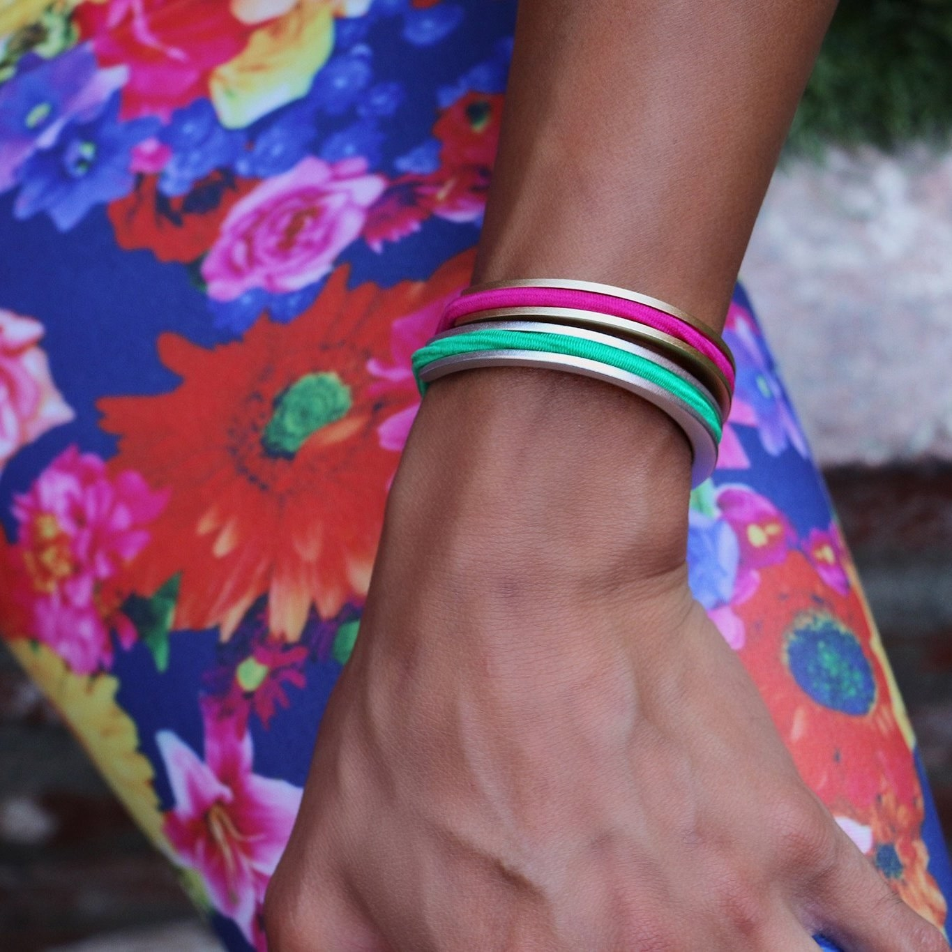 Model wears two cuff bracelets in two different colors