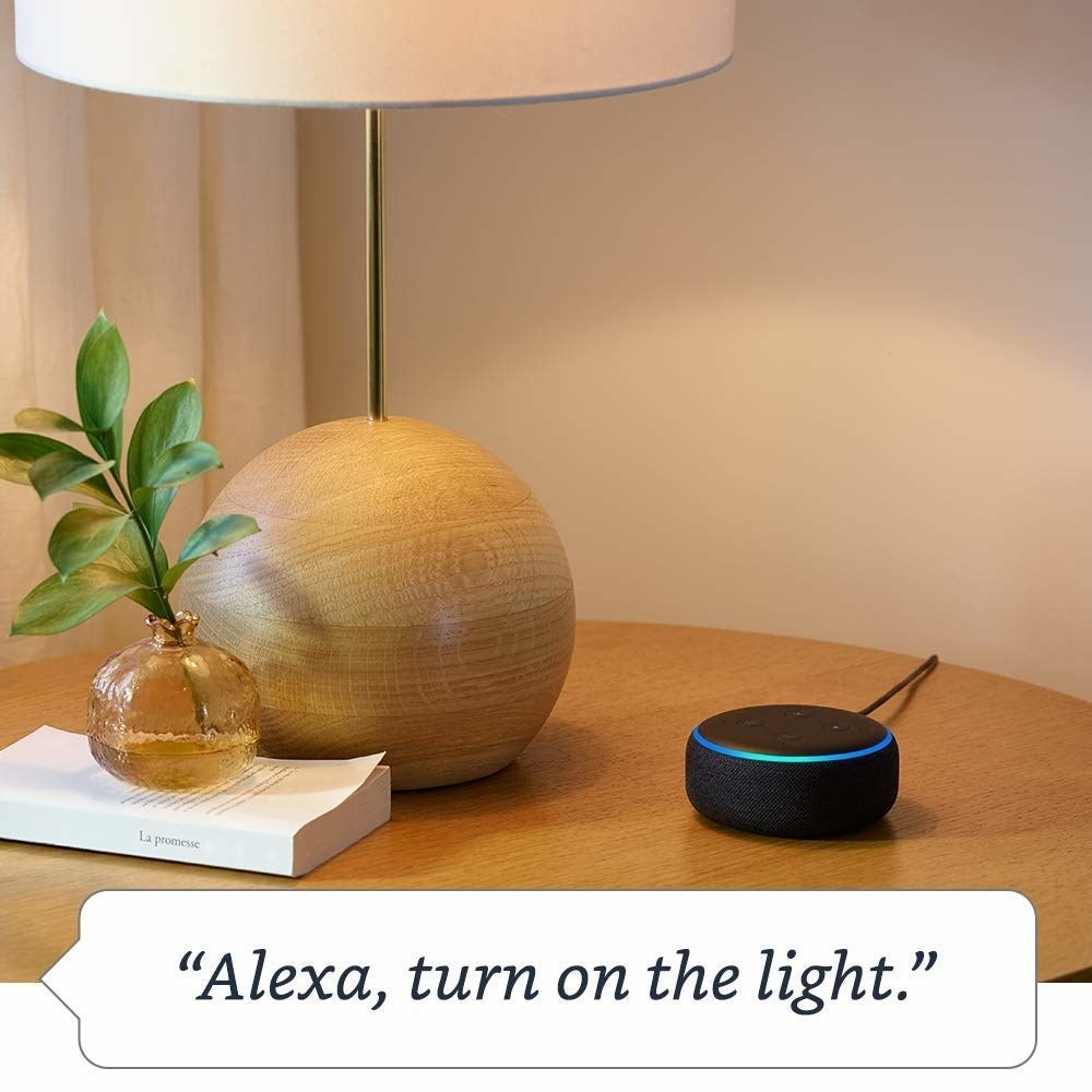"An echo dot sitting on a table with the caption ""Alexa, turn on the light."""