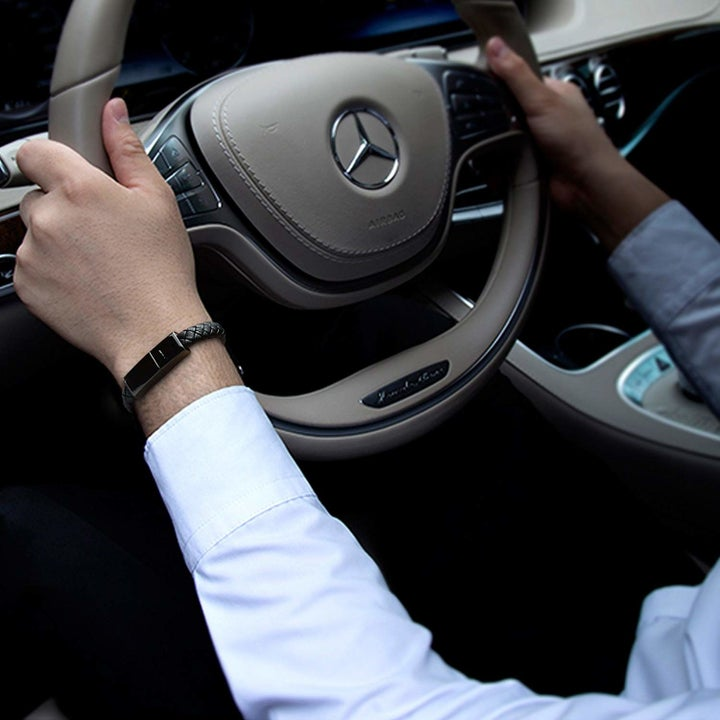 A person wearing the USB bracelet while they drive