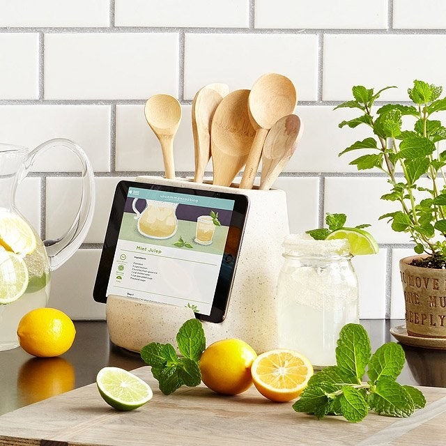 The holder holding an iPad with a recipe on it and also holding wooden spoons