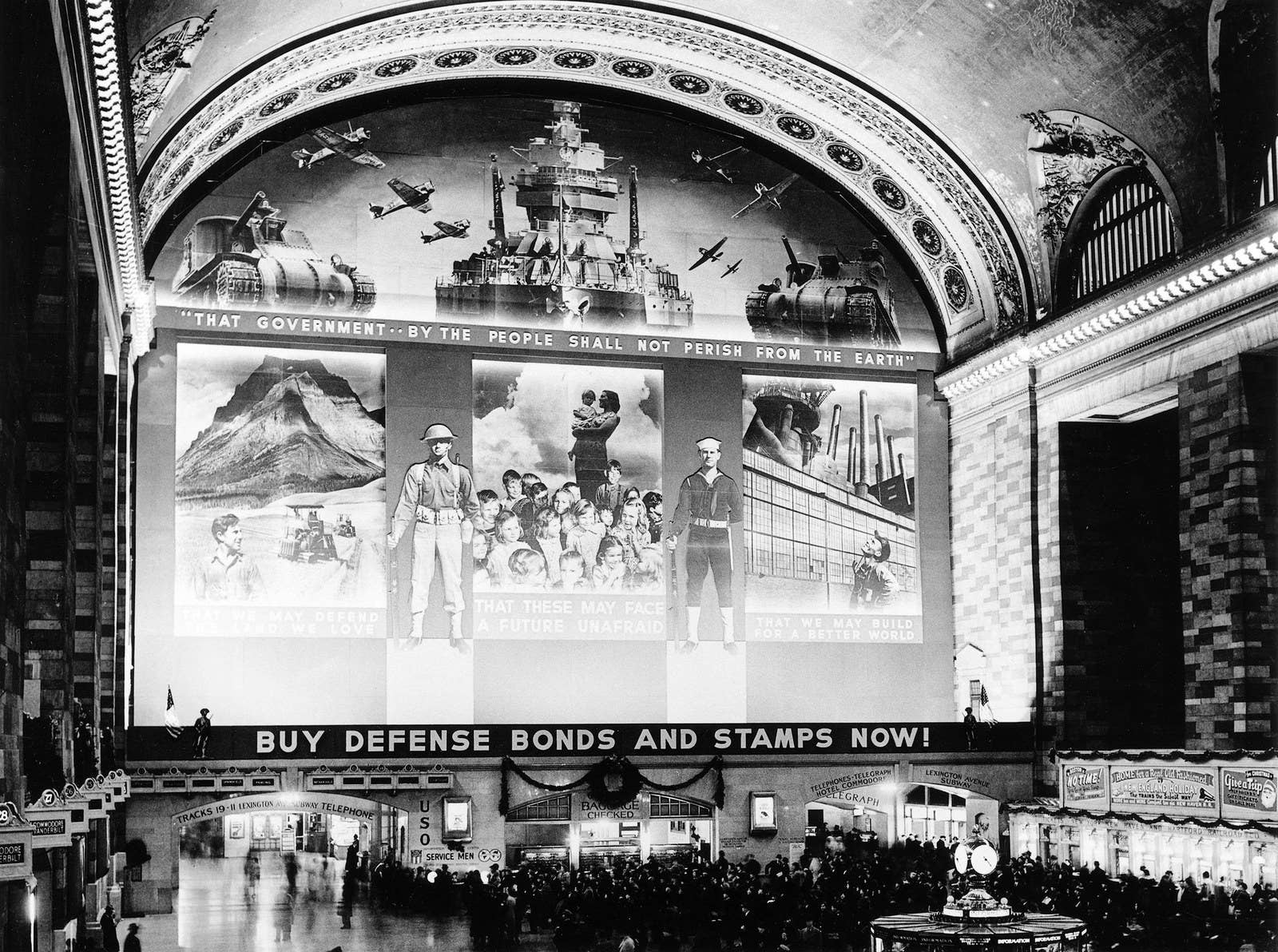 A large advertisement for defense bonds and stamps is hung in New York City's Grand Central Station, circa 1941.